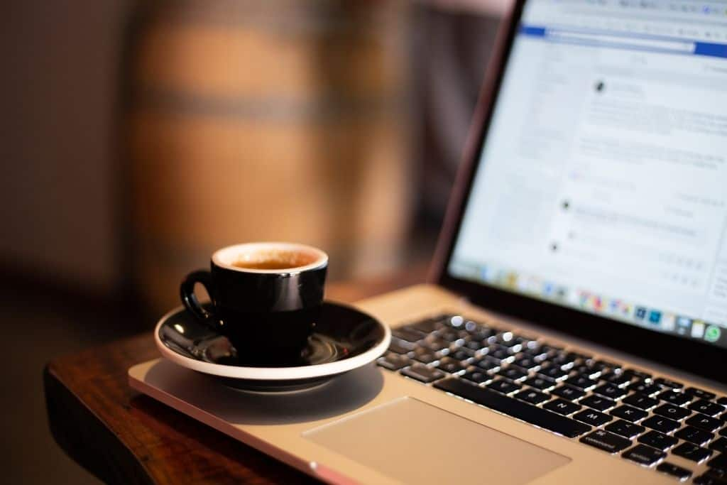 A laptop screen showing a facebook page with a cup of coffe on the laptop