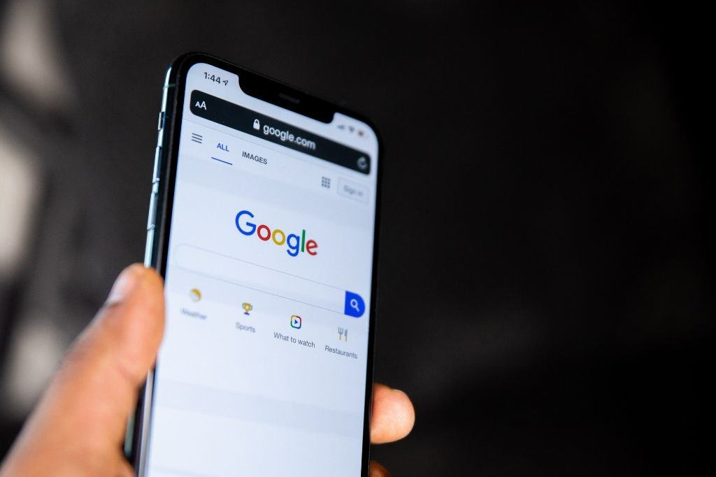 A hand holding up a phone showing a Google search page