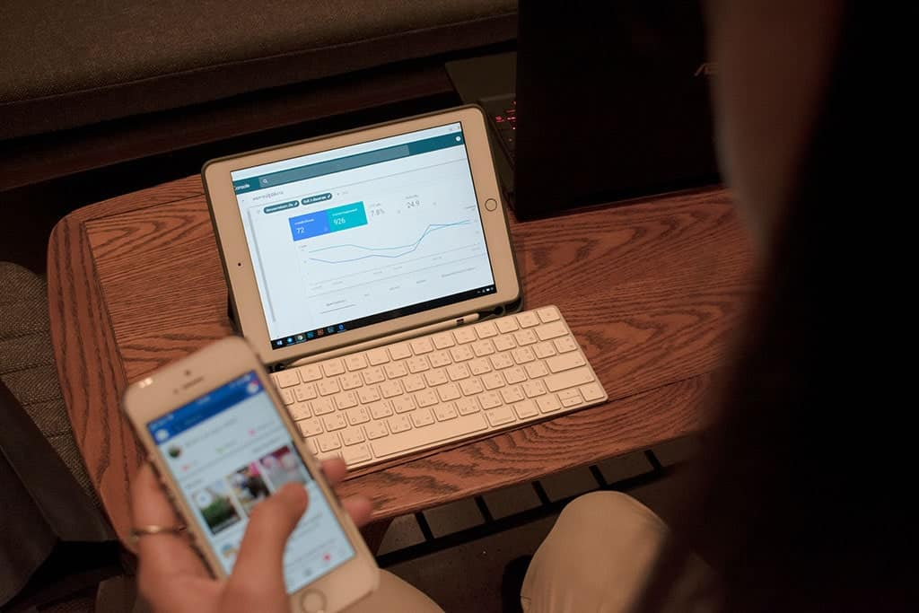 Woman using Google Search Console on mobile in front of laptop