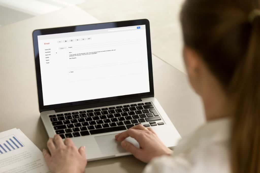 Woman types on a laptop screen